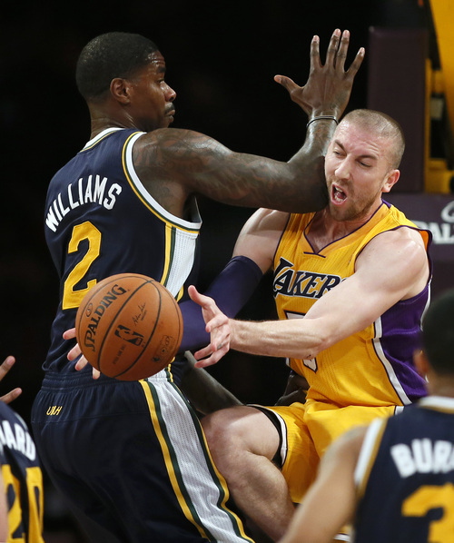 Los Angeles Lakers' Steve Blake, right, takes an elbow in the face from Utah Jazz's Marvin Williams, right, as he passes the ball of to Jordan Hill during the first half of an NBA basketball game in Los Angeles, Tuesday, Feb. 11, 2014. (AP Photo/Danny Moloshok)