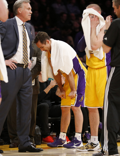 Los Angeles Lakers' Steve Nash, center, pauses near the bench, between coach Mike D'Antoni, left, and Steve Blake, right, as the officials review a call at the end of the first half of an NBA basketball game between the Lakers and the Utah Jazz in Los Angeles, Tuesday, Feb. 11, 2014. (AP Photo/Danny Moloshok)