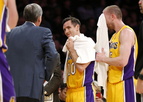 Los Angeles Lakers' Steve Nash, center, looks at coach Mike D'Antoni, left, as Steve Blake, right, wipes his face with a towel as the officials review a call at the end of the first half of an NBA basketball game in Los Angeles, Tuesday, Feb. 11, 2014. (AP Photo/Danny Moloshok)