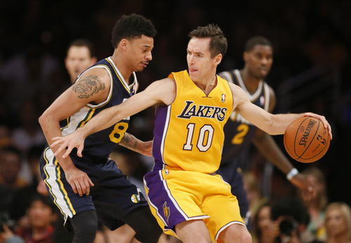 Los Angeles Lakers Steve Nash dribbles the ball as Utah Jazz's Diante Garrett defends during the first half of an NBA basketball game in Los Angeles, Tuesday, Feb. 11, 2014. (AP Photo/Danny Moloshok)