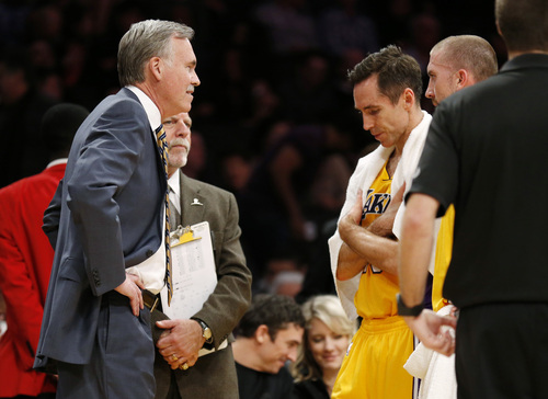 Los Angeles Lakers' Steve Nash looks down while talking with coach Mike D'Antoni, left, as athletic trainer Gary Vitti, left rear, stands with them along with Steve Blake, right, while officials review a call at the end of the first half of an NBA basketball game between the Lakers and the Utah Jazz in Los Angeles, Tuesday, Feb. 11, 2014. (AP Photo/Danny Moloshok)