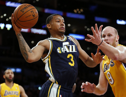 Utah Jazz's Trey Burke, left, passes around Los Angeles Lakers' Chris Kaman during the first half of an NBA basketball game in Los Angeles, Tuesday, Feb. 11, 2014. (AP Photo/Danny Moloshok)