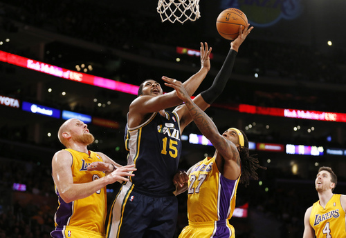 Utah Jazz's Derrick Favors (15) is fouled by Los Angeles Lakers' Chris Kaman, left, as Jordan Hill, center right, also defends and Ryan Kelly (4) watches during the first half of an NBA basketball game in Los Angeles, Tuesday, Feb. 11, 2014. (AP Photo/Danny Moloshok)