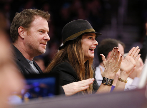 Actress Brooke Shields, right, and her husband, Chris Henchy, left, cheer as they sit courtside at the NBA basketball game between the Utah Jazz and the Los Angeles Lakers in Los Angeles, Tuesday, Feb. 11, 2014. (AP Photo/Danny Moloshok)