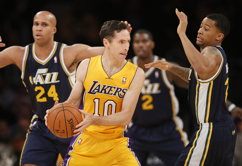 Los Angeles Lakers' Steve Nash, center, looks to pass around Utah Jazz's Trey Burke, right, as Richard Jefferson, left, also defends during the first half of an NBA basketball game in Los Angeles, Tuesday, Feb. 11, 2014. (AP Photo/Danny Moloshok)