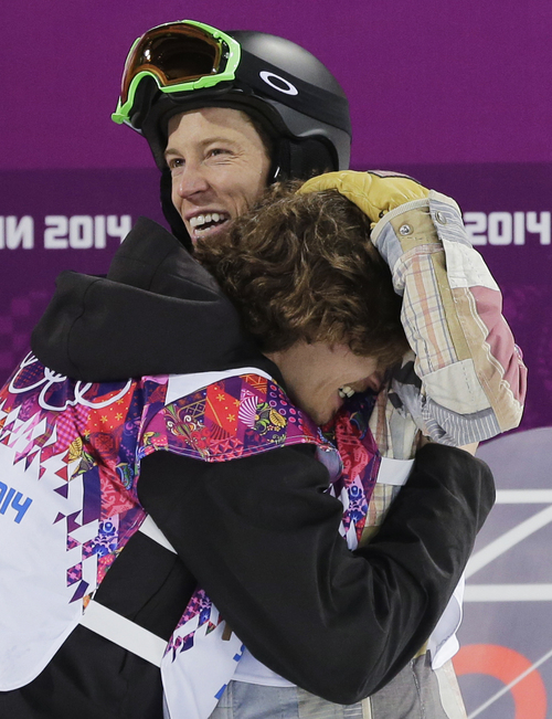 Switzerland's Iouri Podladtchikov, bottom, celebrates with Shaun White of the United States after Podladtchikov won the gold medal in the men's snowboard halfpipe final at the Rosa Khutor Extreme Park, at the 2014 Winter Olympics, Tuesday, Feb. 11, 2014, in Krasnaya Polyana, Russia. (AP Photo/Andy Wong)