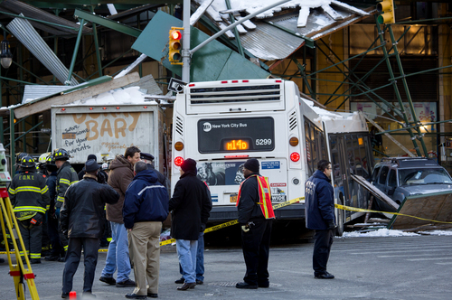 A Metropolitan Transportation Authority bus and a truck rest against scaffolding at 14th Street and 7th Avenue in New York, Wednesday, Feb. 12, 2014, after an early morning collision between the bus and truck. One person was killed and at least four were injured in the crash, that also involved several parked vehicles. (AP Photo/Craig Ruttle)