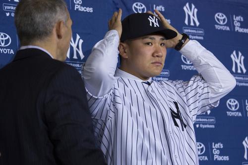 New York Yankees' pitcher Masahiro Tanaka puts on his baseball cap, as manager Joe Girardi looks on,  as he is introduced to the media at Yankee Stadium in New York Tuesday, Feb. 11, 2014. (AP Photo/Craig Ruttle)