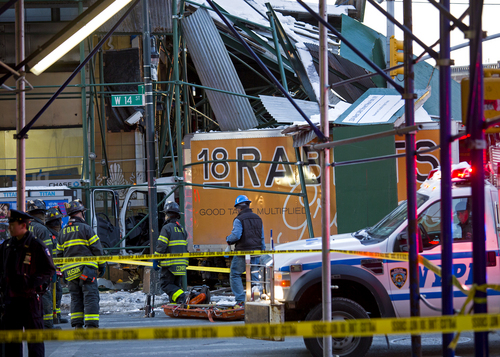 A truck that was involved in a collision with a Metropolitan Transportation Authority bus rests against scaffolding at 14th Street and 7th Avenue in New York, Wednesday, Feb. 12, 2014, after the incident. One person was killed and at least four were injured in the crash, that also involved several parked vehicles. (AP Photo/Craig Ruttle)