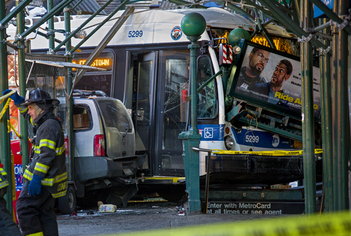 A Metropolitan Transportation Authority bus and another vehicle rest against scaffolding and a subway entrance at 14th Street and 7th Avenue in New York, Wednesday, Feb. 12, 2014, after an early morning collision between a city bus and a truck. One person was killed and at least four were injured in the crash. (AP Photo/Craig Ruttle)