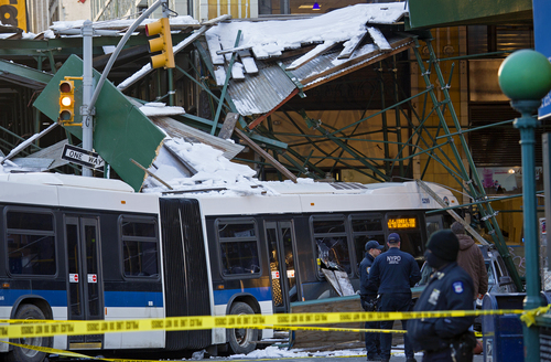 A Metropolitan Transportation Authority bus rests against scaffolding at 14th Street and 7th Avenue in New York, Wednesday, Feb. 12, 2014, after an early morning collision between the city bus and a truck. One person was killed and at least four were injured in the crash. (AP Photo/Craig Ruttle)