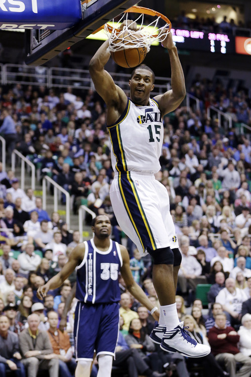 Utah Jazz's Derrick Favors (15) dunks as Oklahoma City Thunder' forward Kevin Durant (35) watches in the second half of an NBA basketball game, Tuesday, Feb. 12, 2013, in Salt Lake City. The Jazz won 109-94. (AP Photo/Rick Bowmer)