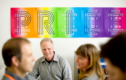 In this  Wednesday, Feb. 12, 2014, photo, workers from Facebook's health center gather near a banner promoting gay pride at the company's Menlo Park, Calif., headquarters. The social media giant is adding a customizable profile option with about 50 different terms people can use to identify their gender. (AP Photo/Noah Berger)