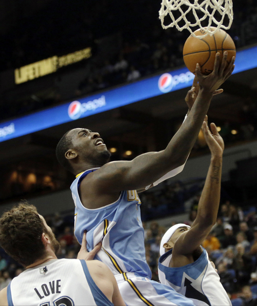 Denver Nuggets's J.J. Hickson lays up a shot as Minnesota Timberwolves' Kevin Love stands near in the second half of an NBA basketball game Wednesday, Feb. 12, 2014, in Minneapolis. The Timberwolves won 117-90. Hickson scored 14 points and had 13 rebounds. (AP Photo/Jim Mone)