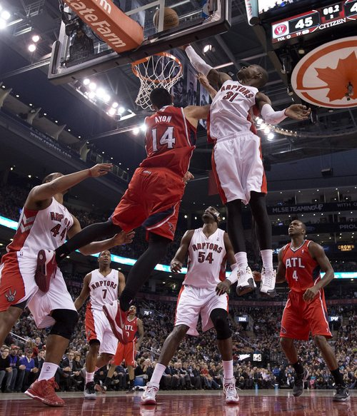 Toronto Raptors guard Terrence Ross (31) tries to guard as Atlanta Hawks center Gustavo Ayon (14) lays up for a basket during first-half NBA basketball game action in Toronto, Wednesday, Feb. 12, 2014. (AP Photo/The Canadian Press, Frank Gunn)