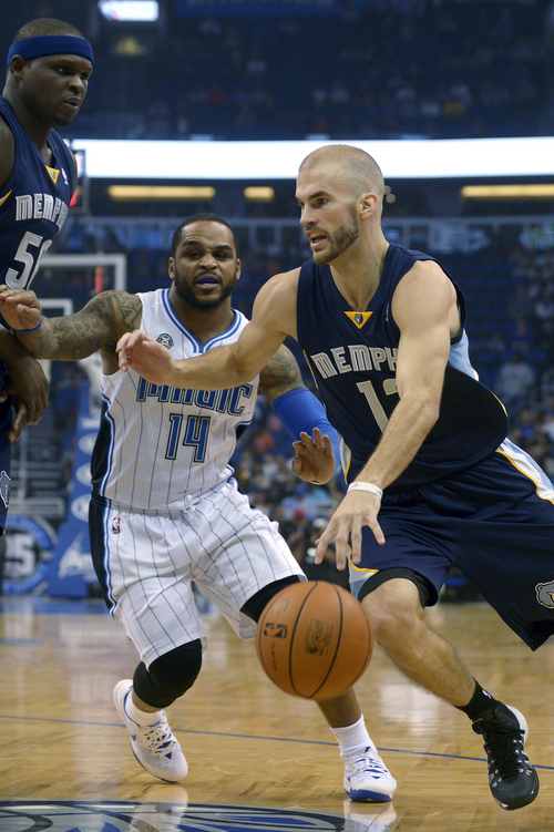 Memphis Grizzlies shooting guard Nick Calathes, right, drives past Orlando Magic point guard Jameer Nelson (14) as forward Zach Randolph (50) watches during the first half of an NBA basketball game in Orlando, Fla., Wednesday, Feb. 12, 2014. (AP Photo/Phelan M. Ebenhack)