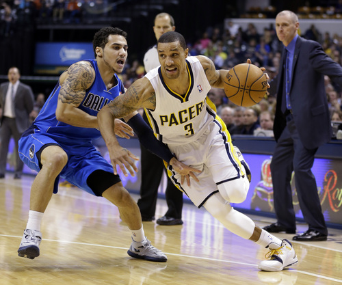 Indiana Pacers guard George Hill, right, drives on Dallas Mavericks guard Shane Larkin during the second half of an NBA basketball game in Indianapolis, Wednesday, Feb. 12, 2014. The Mavericks defeated the Pacers 81-73. (AP Photo/Michael Conroy)