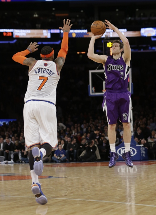 Sacramento Kings' Jimmer Fredette (7) makes a 3-point basket as New York Knicks' Carmelo Anthony (7) runs out to defend during the second half of an NBA basketball game Wednesday, Feb. 12, 2014, in New York. The Kings won 106-101. (AP Photo/Frank Franklin II)