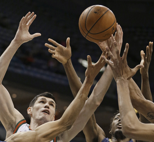 Milwaukee Bucks' Ersan Ilyasova, left, and New Orleans Pelicans' Al-Farouq Aminu reach for a rebound during the first half of an NBA basketball game Wednesday, Feb. 12, 2014, in Milwaukee. (AP Photo/Jeffrey Phelps)