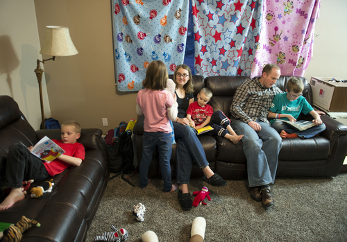 Keith Johnson | The Salt Lake Tribune  Jeremy and Andrea Griggs sit with their 4 children in the living room of the home they are renting in Murray, Utah, February 11, 2014. The Griggs, who have two autistic sons, had to sell the home they built in West Jordan to pay for therapy that isn't covered by insurance in Utah. In 34 other states across the country insurance companies are required by law to offer these benefits.