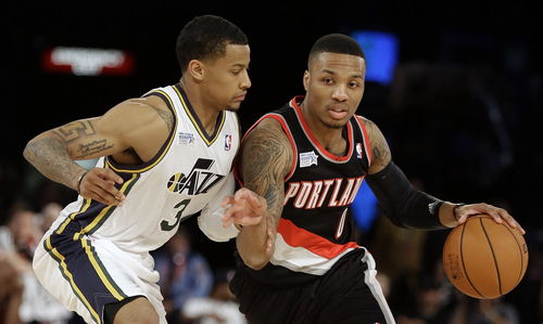 Team Hill's Damian Lillard of the Portland Trail Blazers, right, moves the ball against Team Webber's Trey Burke of the Utah Jazz during the Rising Star NBA All Star Challenge Basketball game, Friday, Feb. 14, 2014, in New Orleans. (AP Photo/Gerald Herbert)