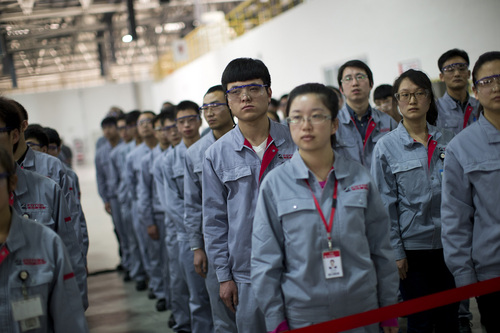 Foton Cummins Engine plant workers look on as U.S. Secretary of State John Kerry makes remarks after touring the plant in Beijing, China Saturday, Feb. 15, 2014. Kerry toured the plant and made remarks on climate change cooperation between the United States and China. (AP Photo/Evan Vucci, Pool)