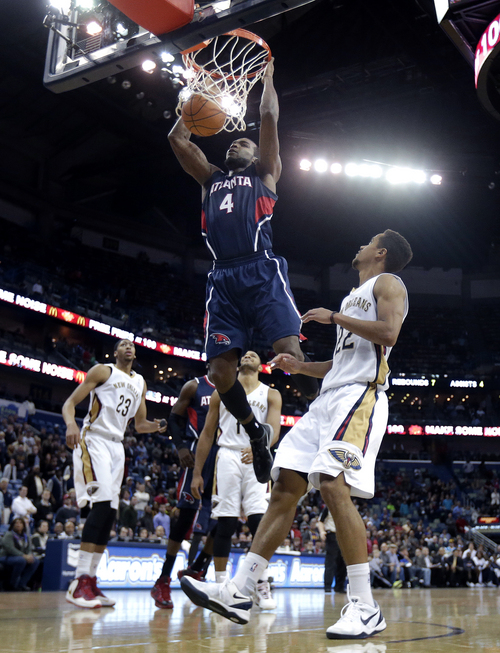 Atlanta Hawks power forward Paul Millsap (4) slam-dunks over New Orleans Pelicans point guard Brian Roberts (22), power forward Anthony Davis (23) and shooting guard Eric Gordon (10) in the second half of an NBA basketball game in New Orleans, Wednesday, Feb. 5, 2014. The Pelicans won 105-100. (AP Photo/Gerald Herbert)