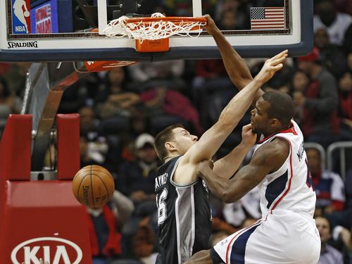 Atlanta Hawks power forward Paul Millsap (4) scores against San Antonio Spurs power forward Aron Baynes (16) in the first half of an NBA  basketball  game  Friday, Jan. 24, 2014, in Atlanta.  (AP Photo/John Bazemore)