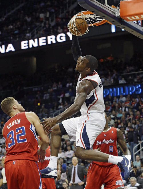 Atlanta Hawks power forward Paul Millsap (4) scores as Los Angeles Clippers power forward Blake Griffin (32) defends in the first half of an NBA basketball game Wednesday, Dec. 4, 2013, in Atlanta.  (AP Photo/John Bazemore)