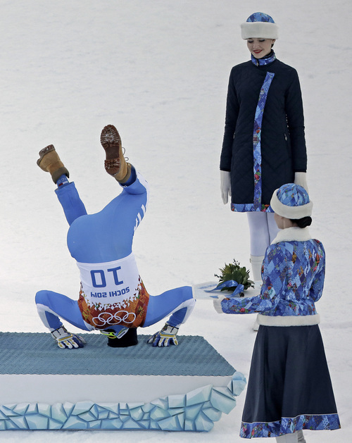 Bronze medalist Italy's Christof Innerhofer does a backflip onto the podium during the flower ceremony for the men's supercombined at the 2014 Winter Olympics, Friday, Feb. 14, 2014, in Krasnaya Polyana, Russia. (AP Photo/Charlie Riedel)