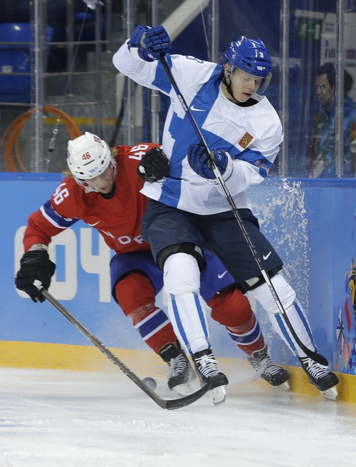 Norway forward Mathis Olimb and Finland defenseman Olli Maatta battle for control of the puck during the 2014 Winter Olympics men's ice hockey game at Shayba Arena, Friday, Feb. 14, 2014, in Sochi, Russia. (AP Photo/Matt Slocum)