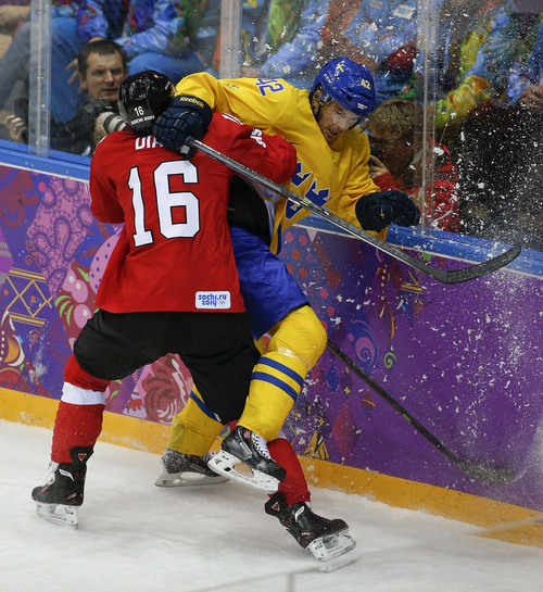 Switzerland defenseman Raphael Diaz checks Sweden forward Jimmie Ericsson in the first period of a men's ice hockey game at the 2014 Winter Olympics, Friday, Feb. 14, 2014, in Sochi, Russia. (AP Photo/Julio Cortez)