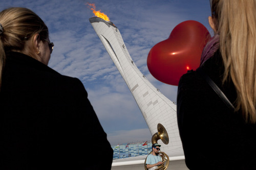 Two women, one holding a heart-shaped Valentine's Day balloon, watch a band perform at the burning Olympic cauldron at the 2014 Winter Olympics, Friday, Feb. 14, 2014, in Sochi, Russia. (AP Photo/Peter Dejong)