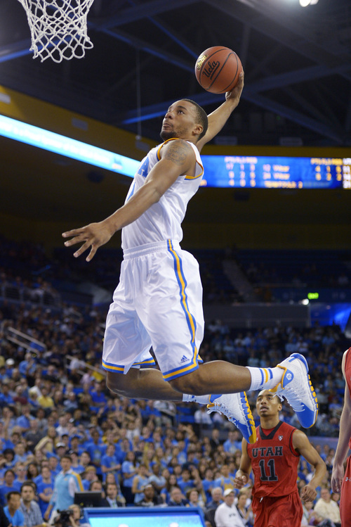 UCLA guard Norman Powell goes in for a dunk as Utah guard Brandon Taylor watches during the second half of an NCAA college basketball game, Saturday, Feb. 15, 2014, in Los Angeles. (AP Photo/Mark J. Terrill)