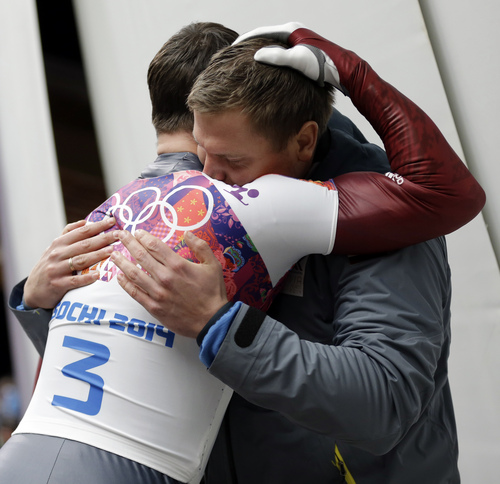 Martins Dukurs of Latvia, left, is hugged by his brother Tomass Dukurs after Martins won the silver medal during the men's skeleton competition at the 2014 Winter Olympics, Saturday, Feb. 15, 2014, in Krasnaya Polyana, Russia. (AP Photo/Natacha Pisarenko)