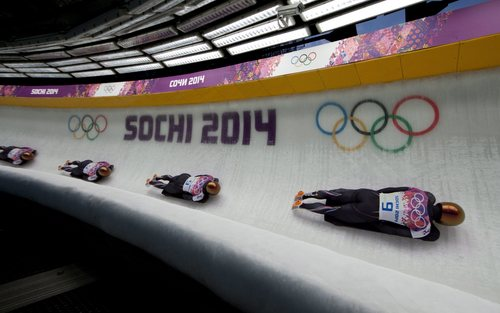 In this image taken with multiple exposures, John Daly of the United States, races down the track at the Sanki Sliding Centre during the men's skeleton competition at the 2014 Sochi Winter Olympics in Krasnaya Polyana, Russia, Saturday, Feb. 15, 2014. Tretiakov won the gold medal in the event. (AP Photo/The Canadian Press, Jonathan Hayward)