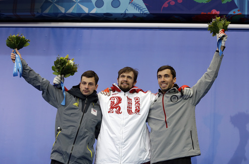 From left to right silver medalist Martins Dukurs of Latvia, gold medalist Alexander Tretiakov of Russia and bronze medalist Matthew Antoine of the United States pose during the flower ceremony after the men's skeleton competition at the 2014 Winter Olympics, Saturday, Feb. 15, 2014, in Krasnaya Polyana, Russia. (AP Photo/Natacha Pisarenko)