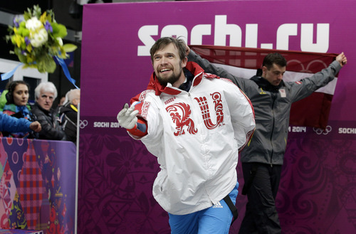 Alexander Tretiakov of Russia tosses his flowers after the ceremony for winning the gold medal in the men's skeleton competition at the 2014 Winter Olympics, Saturday, Feb. 15, 2014, in Krasnaya Polyana, Russia. Walking behind him is silver medalist Martins Dukurs of Latvia. (AP Photo/Michael Sohn)