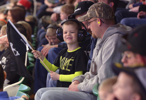 "Leah Hogsten  |  The Salt Lake Tribune Tyler Gilmore of Lyman, Wyo., and his son Jaxson, 4, are entertained by Monster trucks roaring throughout EnergySolutions Arena, Saturday, February 15, 2014, during "" Monster Jam,"" going on through Sunday."
