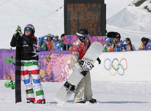 Lindsey Jacobellis, center,  of the United States walks off after crashing in the second semifinal of the women's snowboard cross at the Rosa Khutor Extreme Park, at the 2014 Winter Olympics, Sunday, Feb. 16, 2014, in Krasnaya Polyana, Russia. At left is Italy's Michela Moioli. (AP Photo/Andy Wong)
