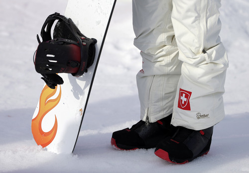 Switzerland's Simona Meiler waits with her board after a seeding run during women's snowboard cross competition at the Rosa Khutor Extreme Park, at the 2014 Winter Olympics, Sunday, Feb. 16, 2014, in Krasnaya Polyana, Russia. (AP Photo/Andy Wong)