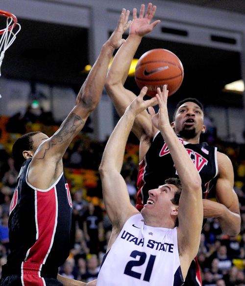 Utah State's Spencer Butterfield (21) has his shot blocked by UNLV's Bryce Dejean-Jones, left, and Khem Birch during an NCAA college basketball game on Saturday, Feb. 15, 2014, in Logan, Utah. (AP Photo/Herald Journal, John Zsiray)