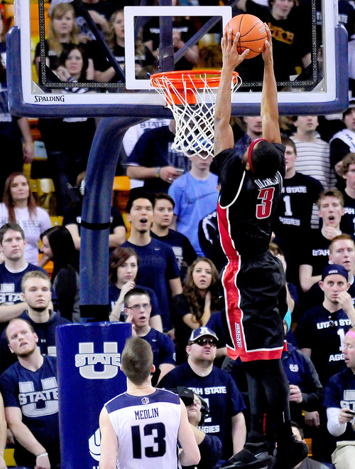 UNLV's Kevin Olekaibe (3) dunks the ball over Utah State's Preston Medlin during an NCAA college basketball game on Saturday, Feb. 15, 2014, in Logan, Utah. (AP Photo/Herald Journal, John Zsiray)