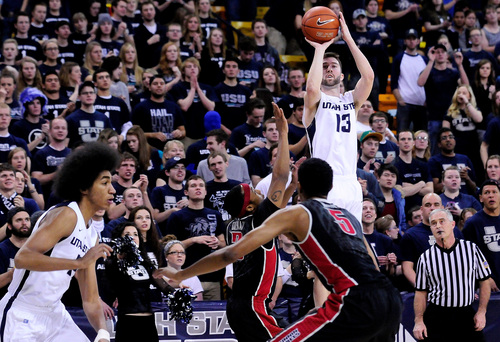 Utah State's Preston Medlin (13) lines up to shoot over UNLV's Kevin Olekaibe and Christian Wood (5) during an NCAA college basketball game on Saturday, Feb. 15, 2014, in Logan, Utah. (AP Photo/Herald Journal, John Zsiray)
