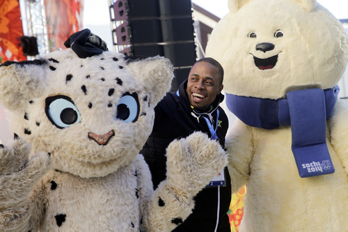Jamaican bobsled brakeman Marvin Dixon poses with the Olympic mascots after a welcome ceremony at the Mountain Olympic Village prior to the 2014 Winter Olympics, Thursday, Feb. 6, 2014, in Krasnaya Polyana, Russia. (AP Photo/Jae C. Hong)