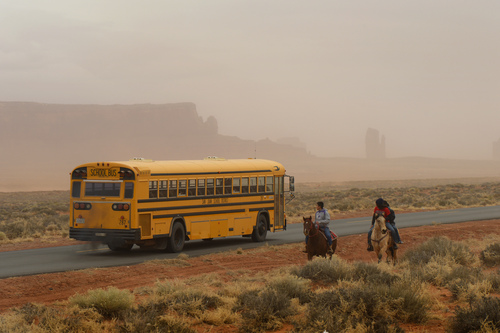 Rick Egan  | The Salt Lake Tribune   A school bus from Monument Valley High School passes Jaydon Yazzie, VanteJren Atene and McKalette Clark, as they ride home from school on their horses onThursday, January 30, 2014.
