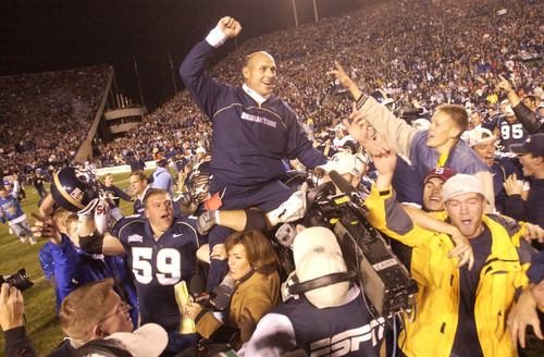 BYU Coach Gary Crowton is hoisted on the players shoulders to celebrate after  BYU defeated the Utes 21-24      photo by Rick Egan  11/17/2001
