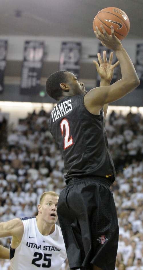 San Diego State guard Xavier Thames (2) takes a shot as Utah State center Jordan Stone (25) defends in the first half of an NCAA college basketball game Saturday, Jan. 25, 2014, in Logan, Utah. (AP Photo/Eli Lucero)