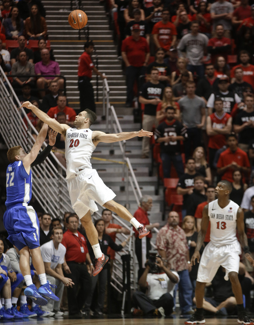 San Diego State forward JJ O'Brien blocks the shot of Air Force's Max Yon  during the second half of San Diego State's 64-56 victory in an NCAA college basketball game Saturday, Feb. 15, 2014, in San Diego. (AP Photo/Lenny Ignelzi)