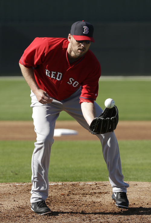 Boston Red Sox pitcher John Lackey performs field drills during spring training baseball practice, Monday, Feb. 17, 2014, in Fort Myers, Fla. (AP Photo/Steven Senne)